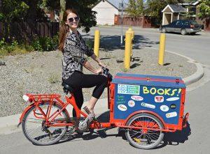 Woman riding a bike bookmobile.
