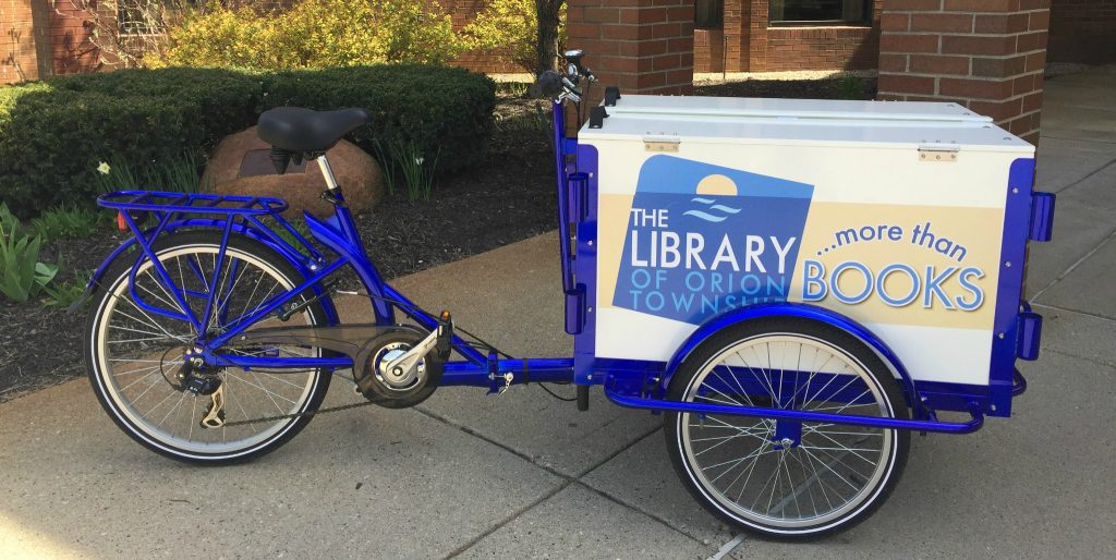 Library Bookbike parked in front of the library building.