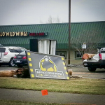 Damaged Buffalo Wild Wings sign, snapped poles, downed lines and vehicle damage.