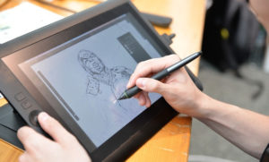 Artist drawing a comic character on a digital tablet