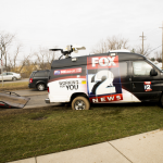 Fox 2 News van stuck in mushy grass in front of Walgreens on M24 during post-storm coverage.