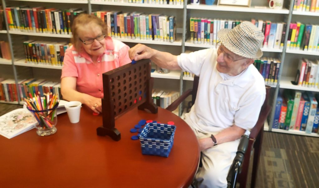Two seniors playing Connect Four.