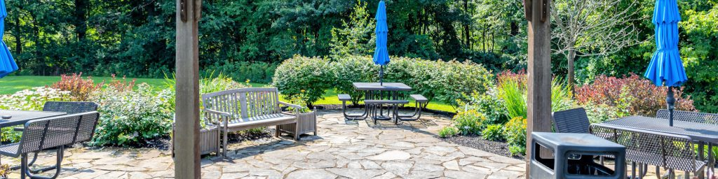 Reading garden with stone pavers, tables, and benches.