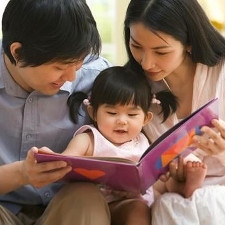 Toddler looking at a book with mother and father